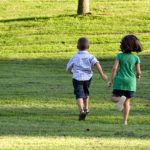 a-little-boy-and-girl-run-through-the-grassy-field-image